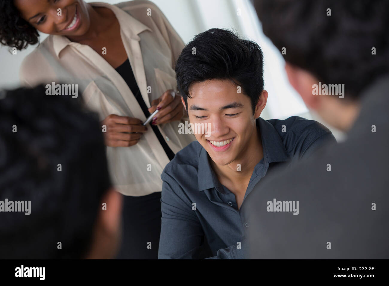 Informal portrait of young male office worker with colleagues - Stock Image