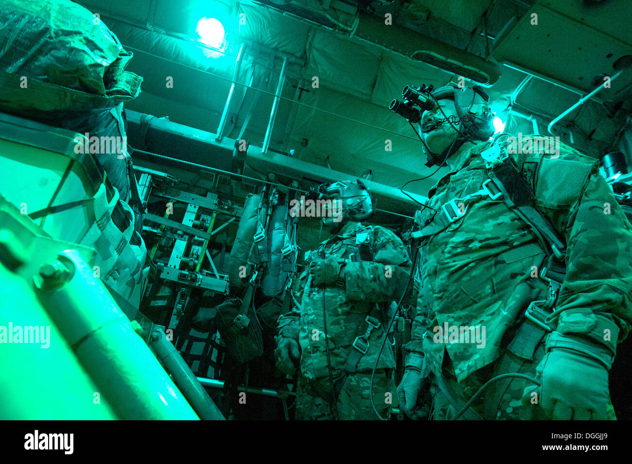 Senior Airman Larry Webster and Tech Sgt. Richard Mulhollen, 774th Expeditionary Airlift Squadron C-130H Hercules loadmasters, wait for the go-ahead to release cargo over a remote drop zone in Ghazni Province, Afghanistan Oct. 7, 2013. Webster, a Lyons, C - Stock Image