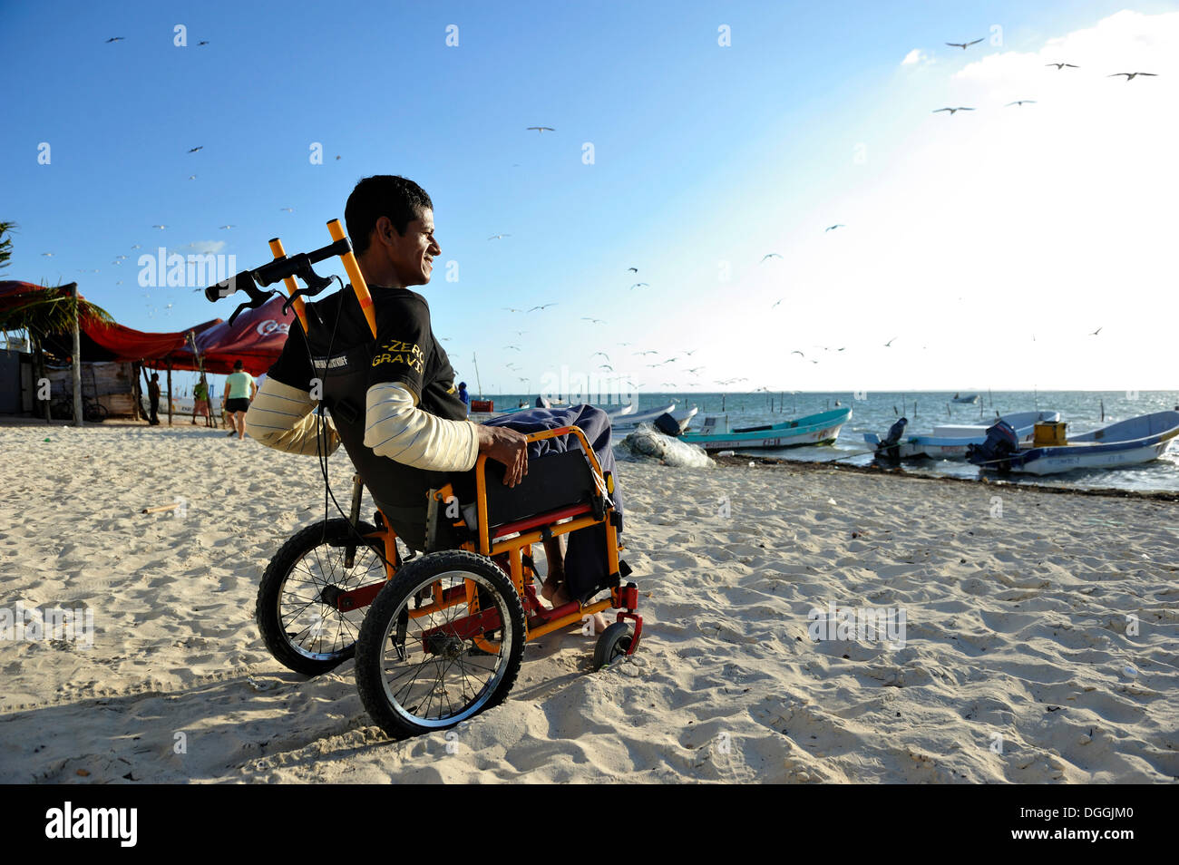 Lobster fisherman suffering from the bends after a diving accident sitting in his wheelchair at the beach, Cancun - Stock Image