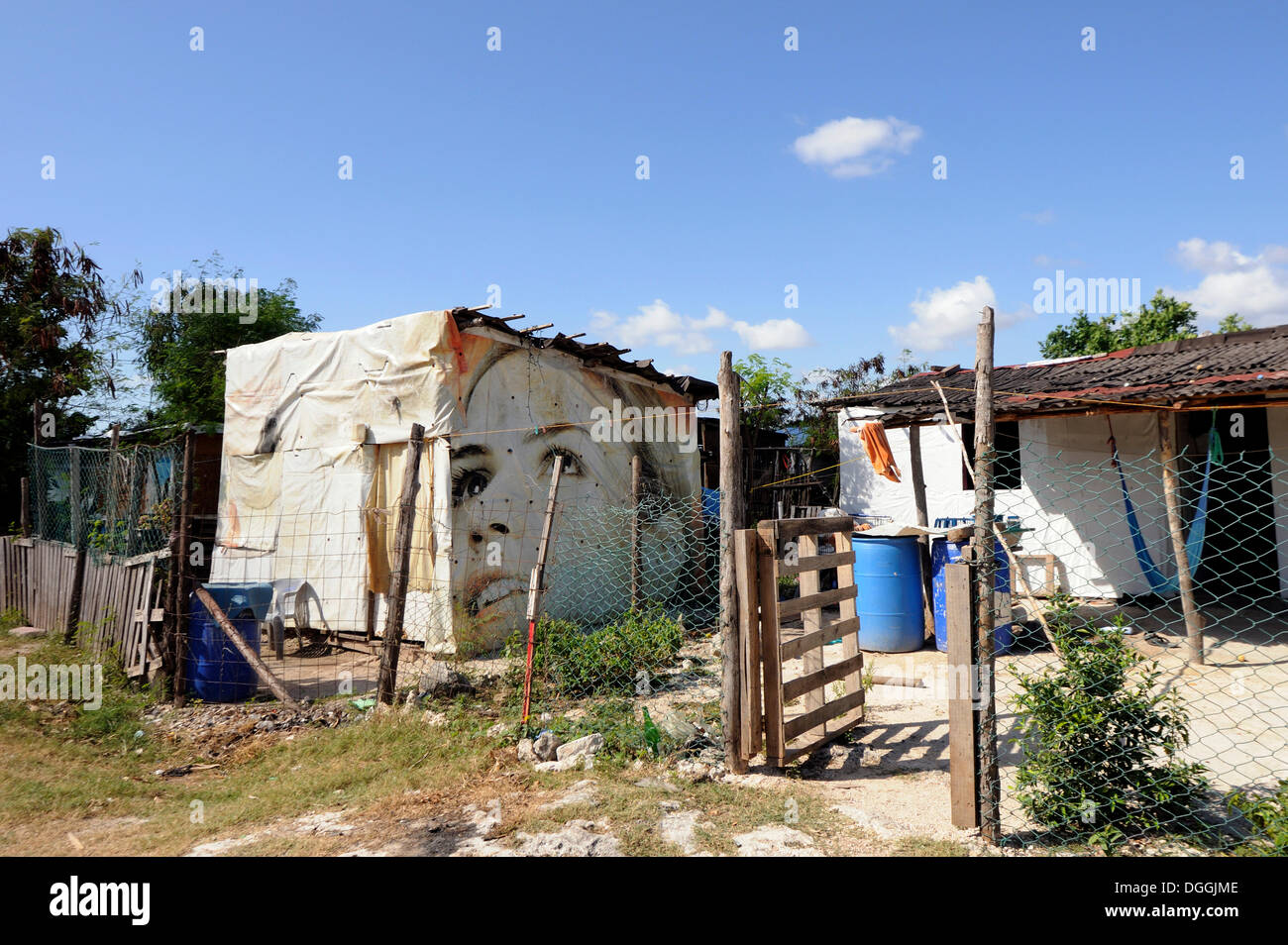 Billboard with the face of a female model serves as an outer wall of a humble cottage in a slum, Cancun, Yucatan Peninsula - Stock Image