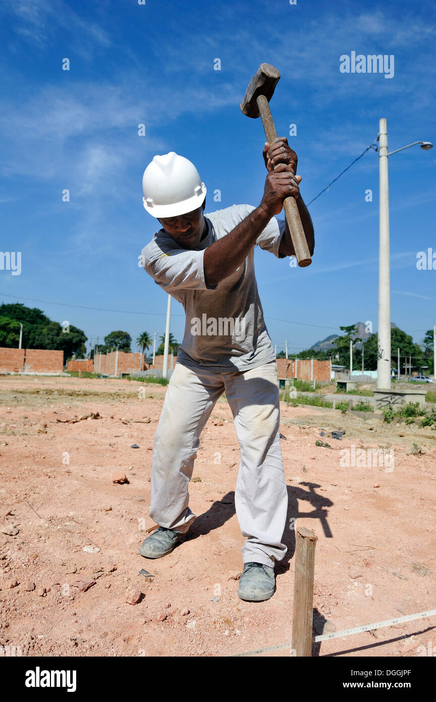 Man with a sledge hammer hitting a peg in the ground, people from the slums, favelas, working together on a building site of the - Stock Image