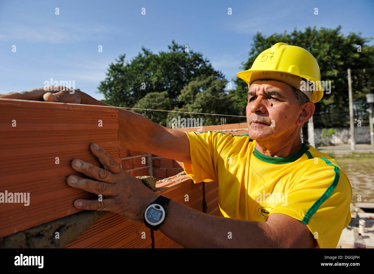 Man with a hard hat working on a building site of the 'Esperanca' housing co-operative, each family helping out on the project - Stock Image
