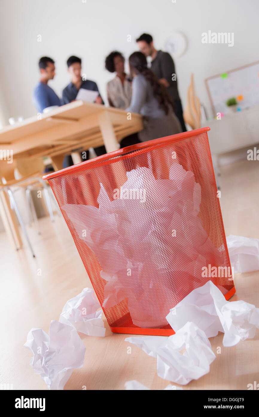 Office waste paper basket and crumpled paper - Stock Image