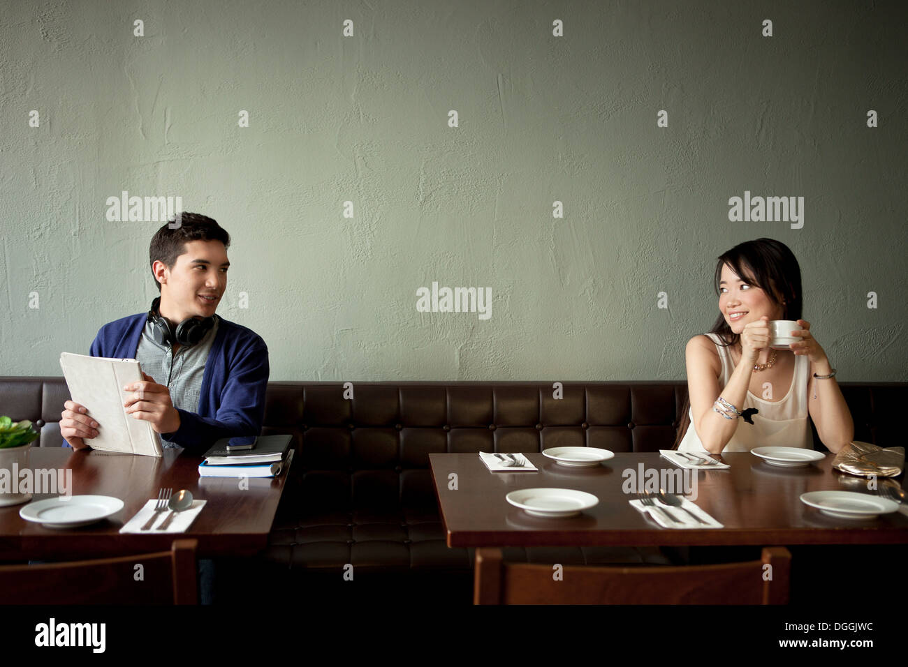 Young man and young woman smiling at each other in restaurant - Stock Image