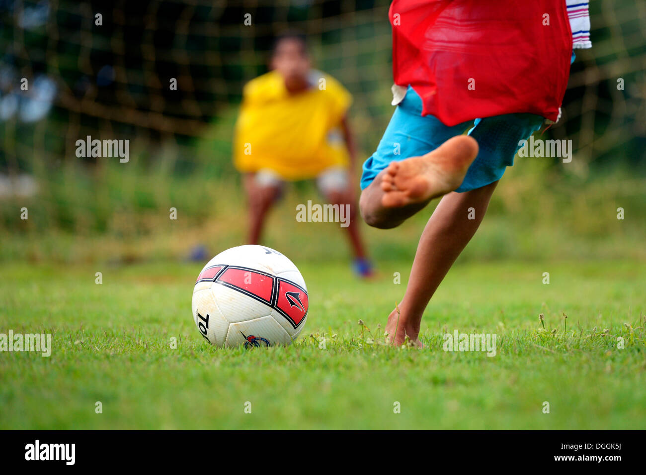 Barefoot boy taking a penalty kick, social project in a favela, Poxoréo, Mato Grosso, Brazil - Stock Image