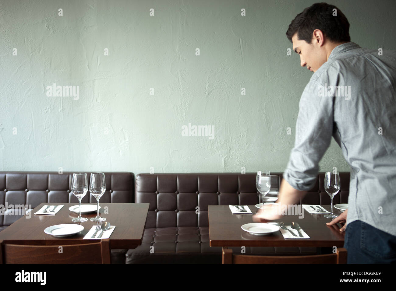 Waiter setting table in restaurant - Stock Image