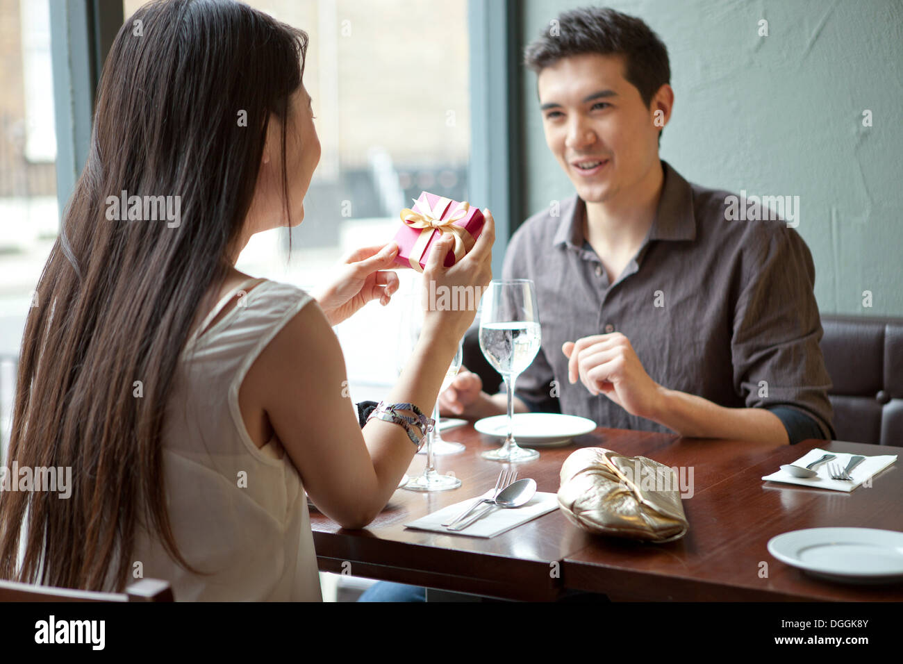 Young couple in restaurant, woman holding gift box Stock Photo