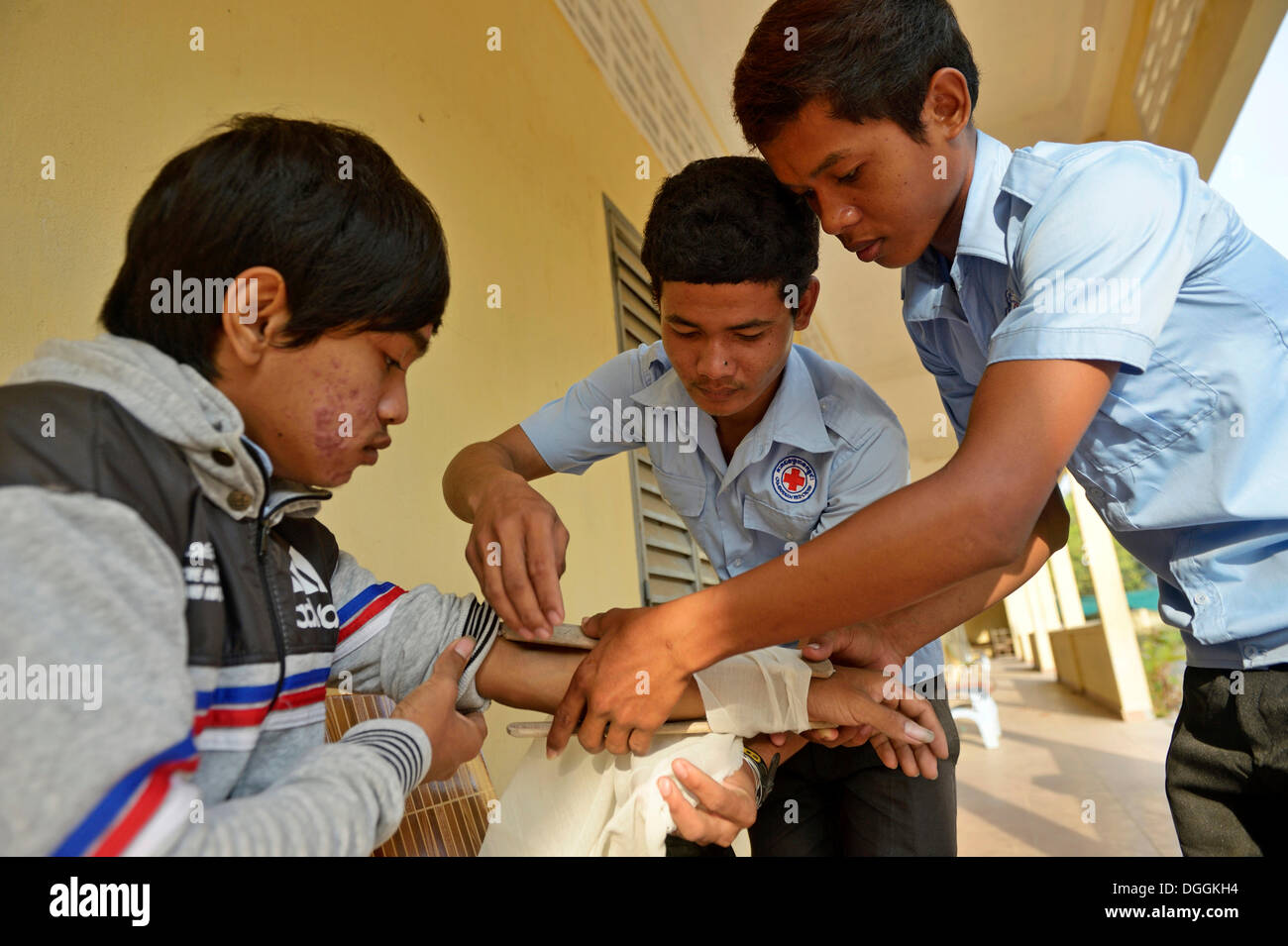 Applying a pressure bandage, training of young people from the community to become first aid workers by the Red - Stock Image