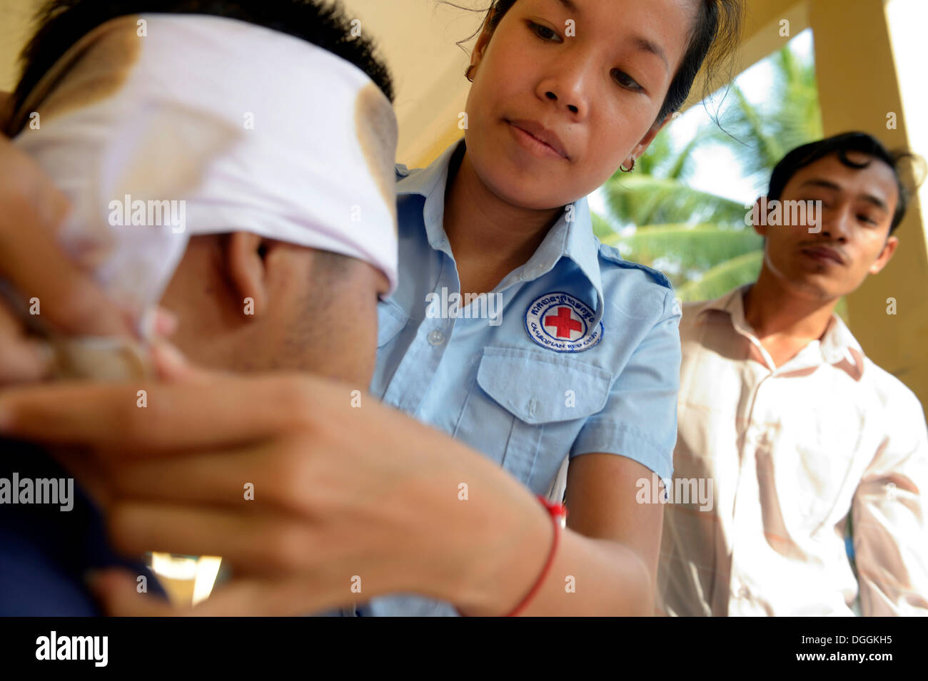 Young woman applying a head bandage, training of young people from the community to become first aid workers by - Stock Image