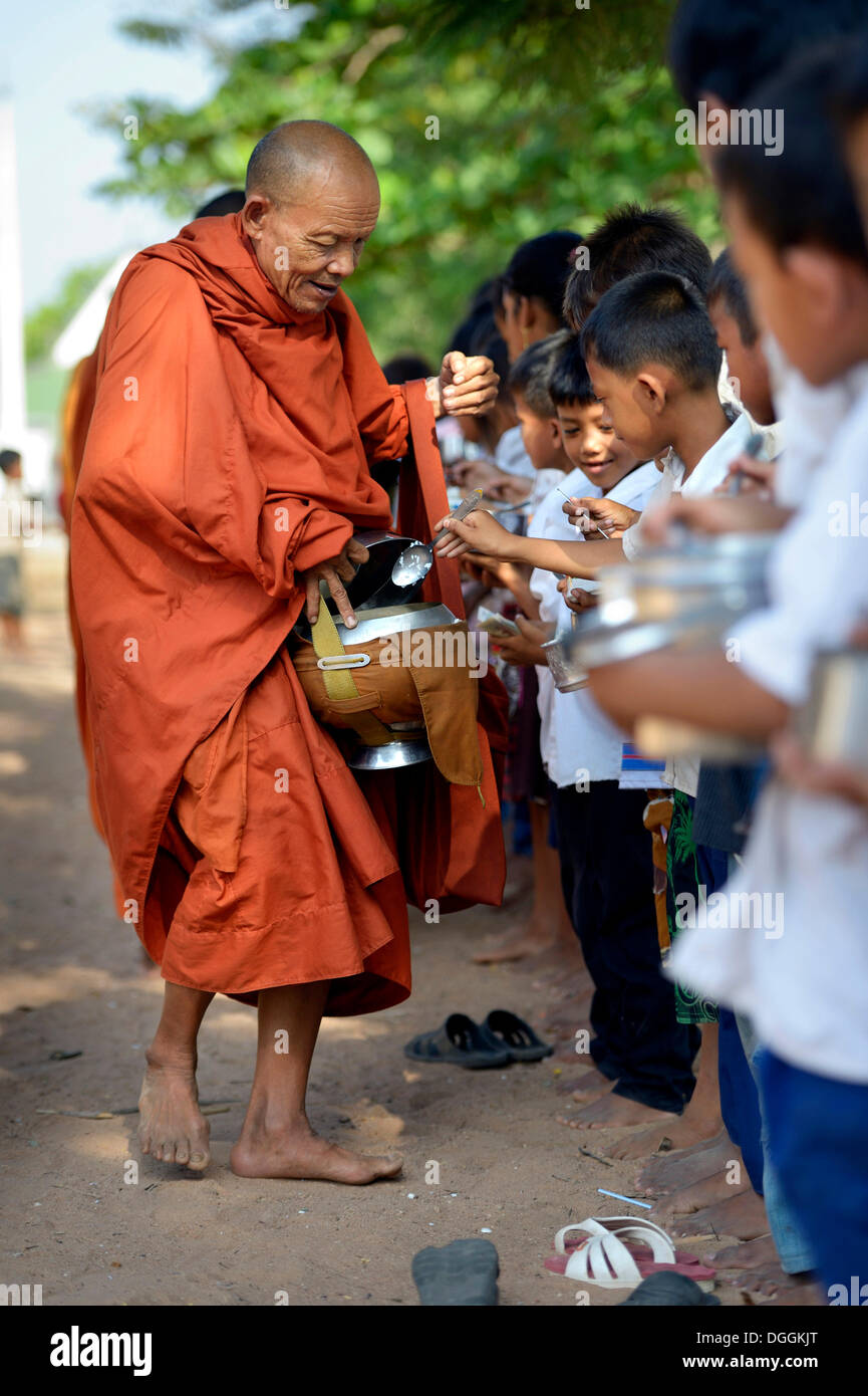 Children donating food and money to a Buddhist monk, traditional ceremony as part of the celebration of the Cambodian New Year - Stock Image
