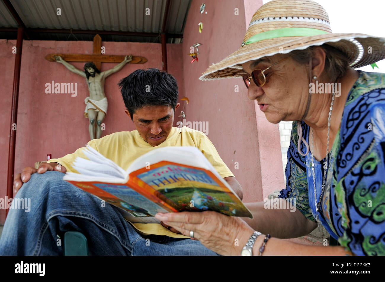 Elderly woman with sun hat teaching a young migrant to read, in a shelter for Latin American migrants, Ixtepec, Oaxaca, Mexico - Stock Image