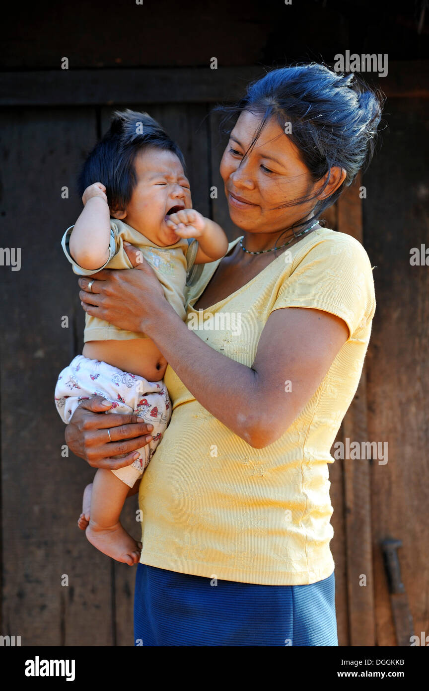 Young mother holding a crying child in her arms, in a community of Guarani Indians, Jaguary, Caaguazú Department, Paraguay - Stock Image