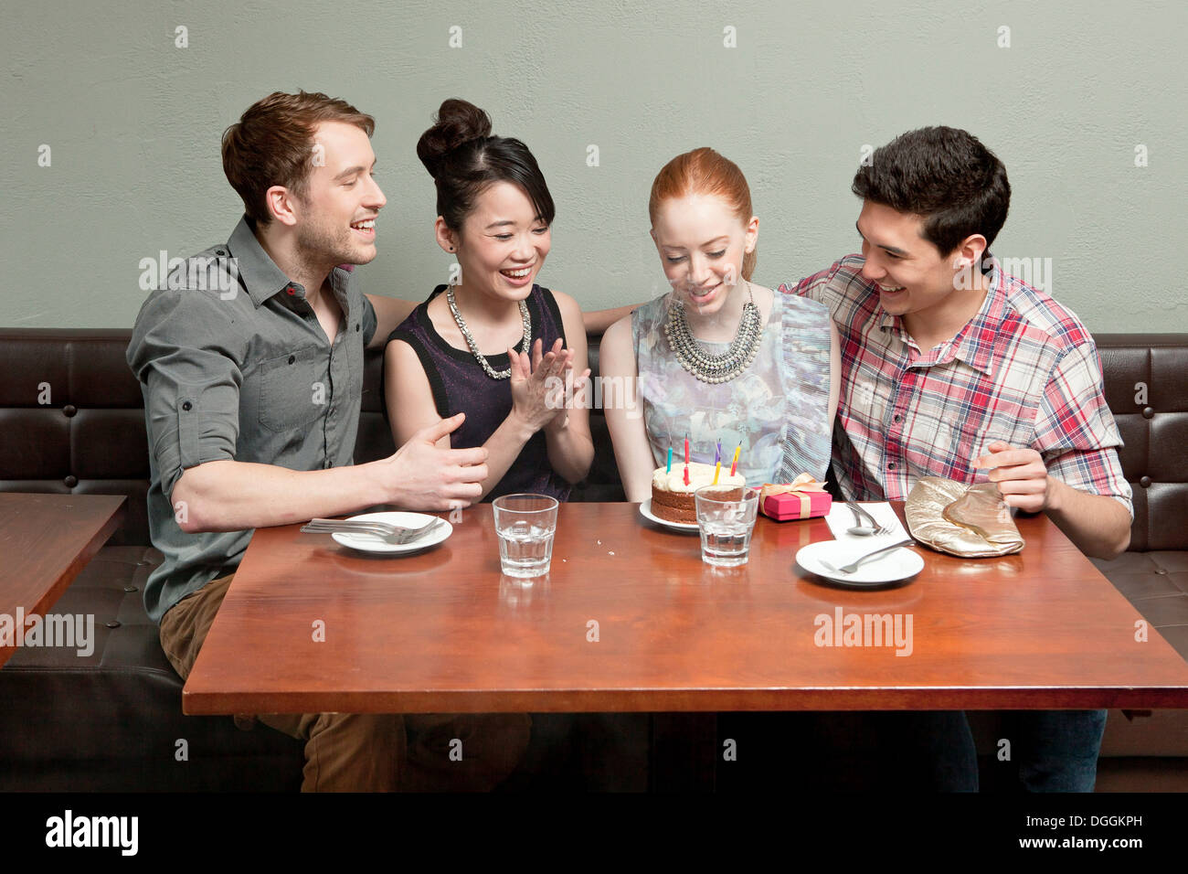 Four friends celebrating birthday in restaurant Stock Photo