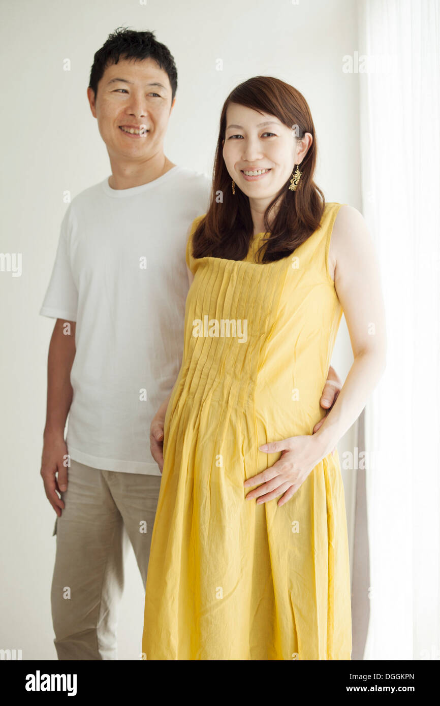 Pregnant woman with man, portrait - Stock Image