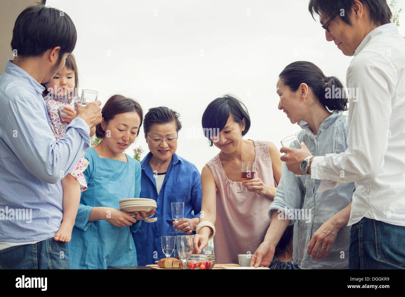 Three generation family eating meal outdoors - Stock Image
