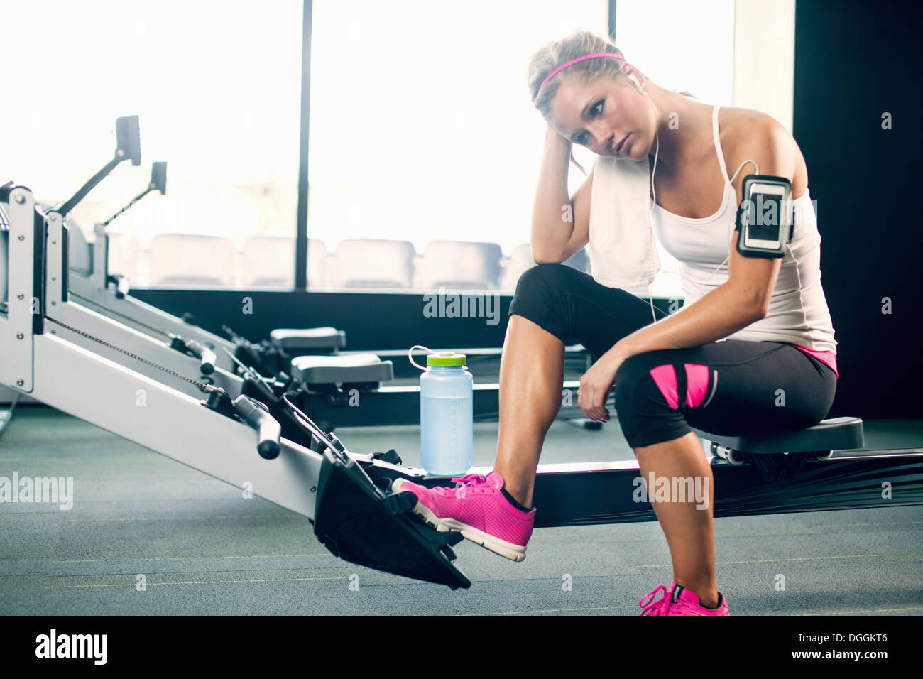 Young woman taking a break from exercising in gym - Stock Image
