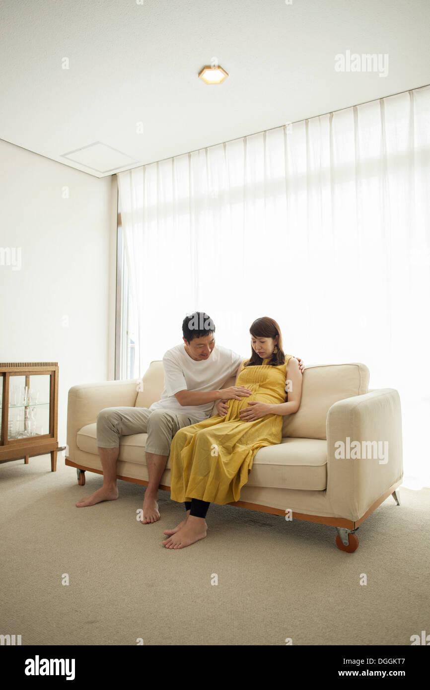 Man touching pregnant woman's stomach on sofa - Stock Image