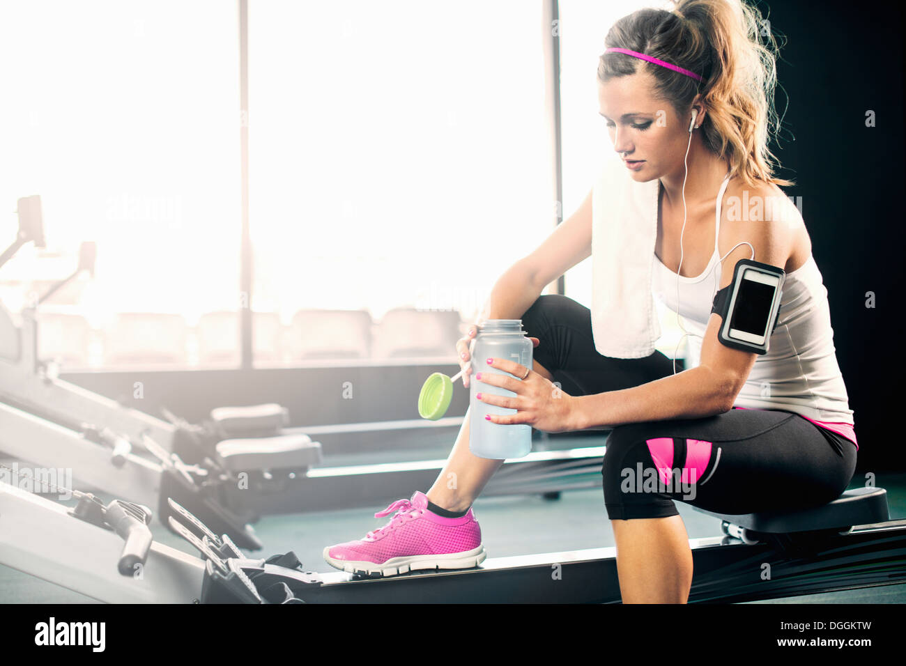 Young woman holding water bottle in gym Stock Photo