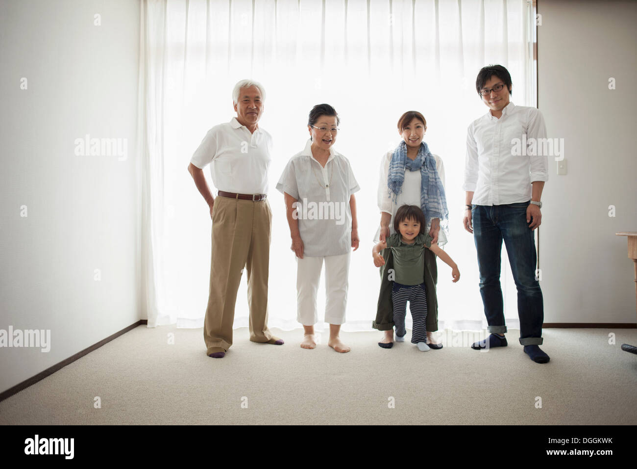 Three generation family standing by window, portrait - Stock Image