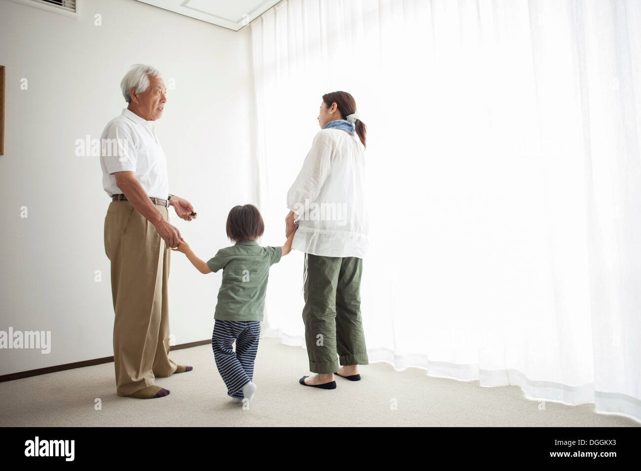 Three generation family standing by window holding hands - Stock Image