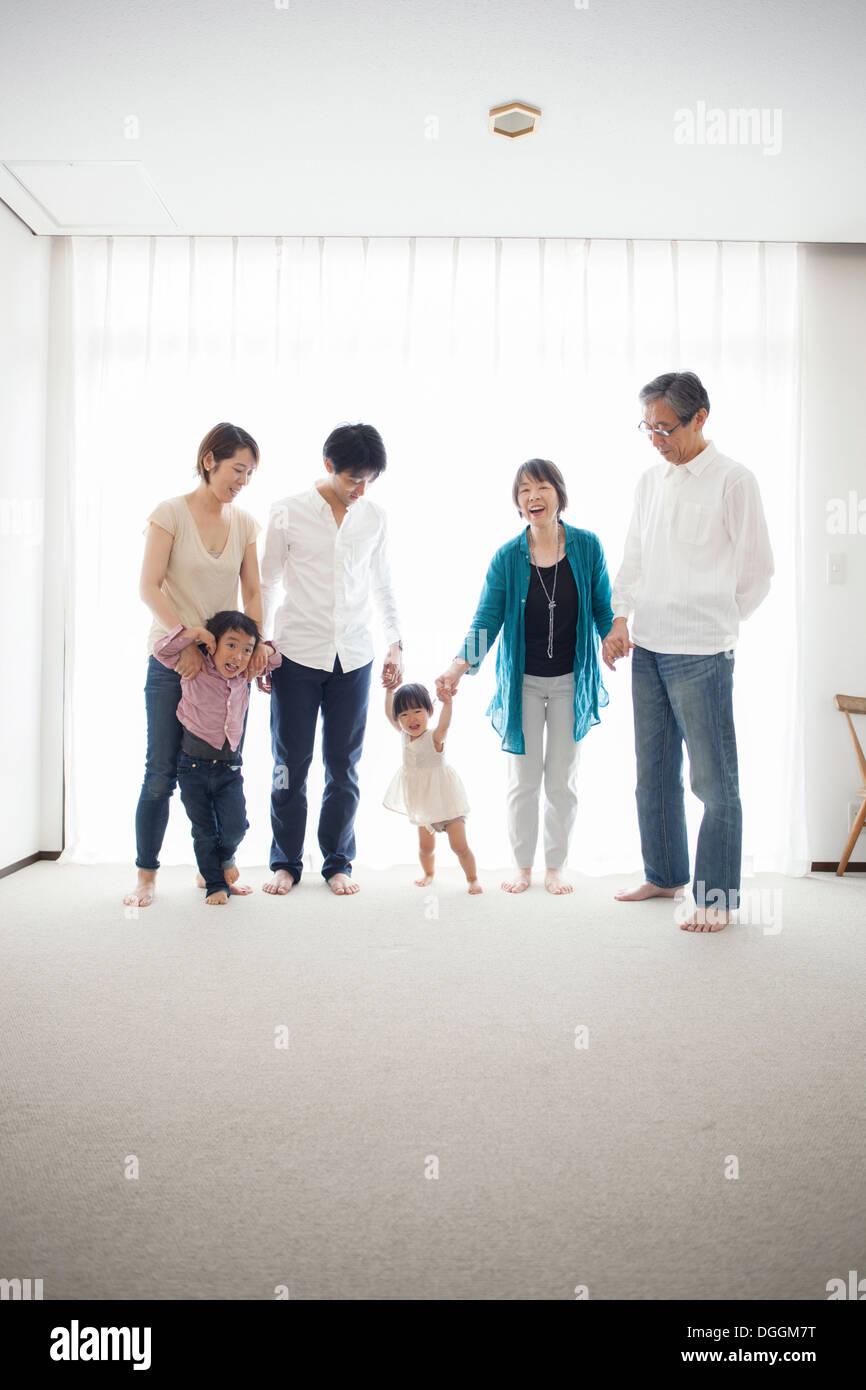 Three generation family holding hands, portrait - Stock Image