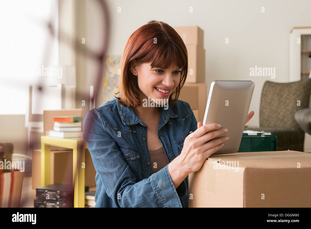 Portrait of woman holding digital tablet amongst cardboard boxes - Stock Image