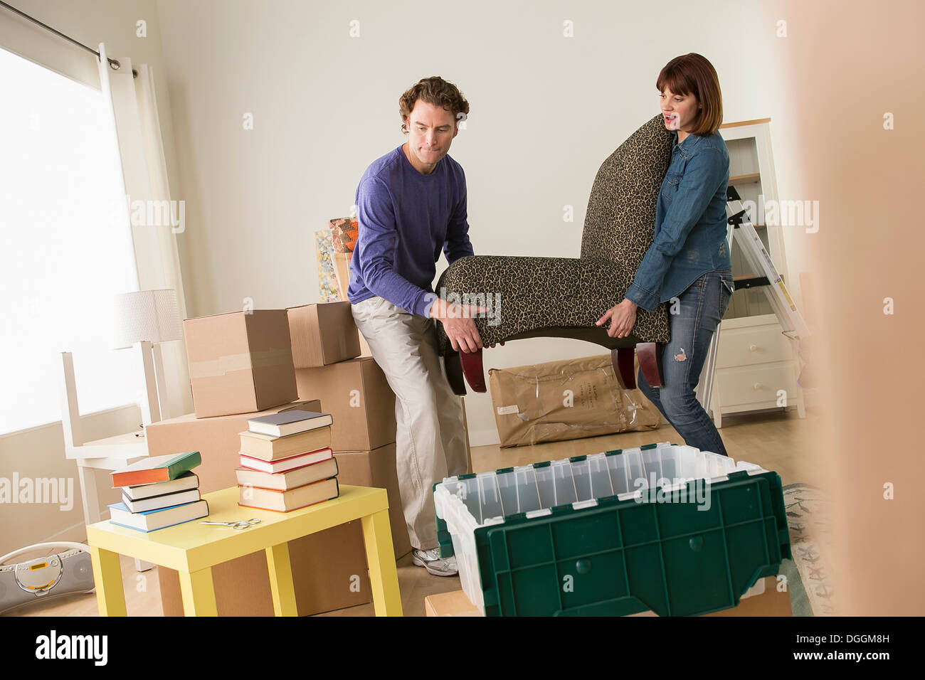 Couple lifting chair in house move - Stock Image