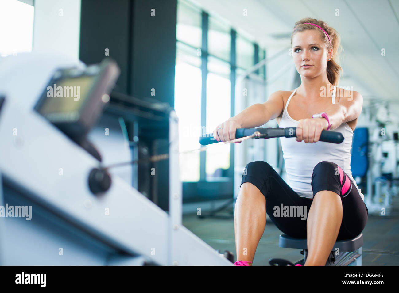 Young woman using rowing machine in gym - Stock Image