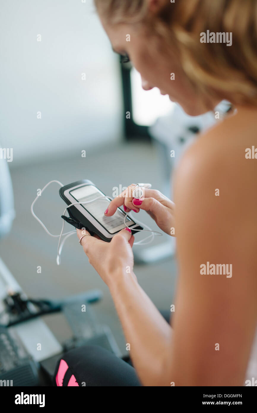 Young woman using mobile while exercising in gym - Stock Image
