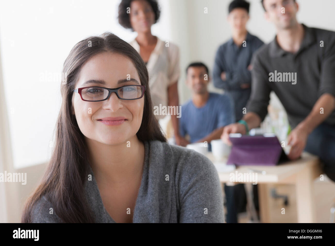 Portrait of young female office worker in front of colleagues - Stock Image