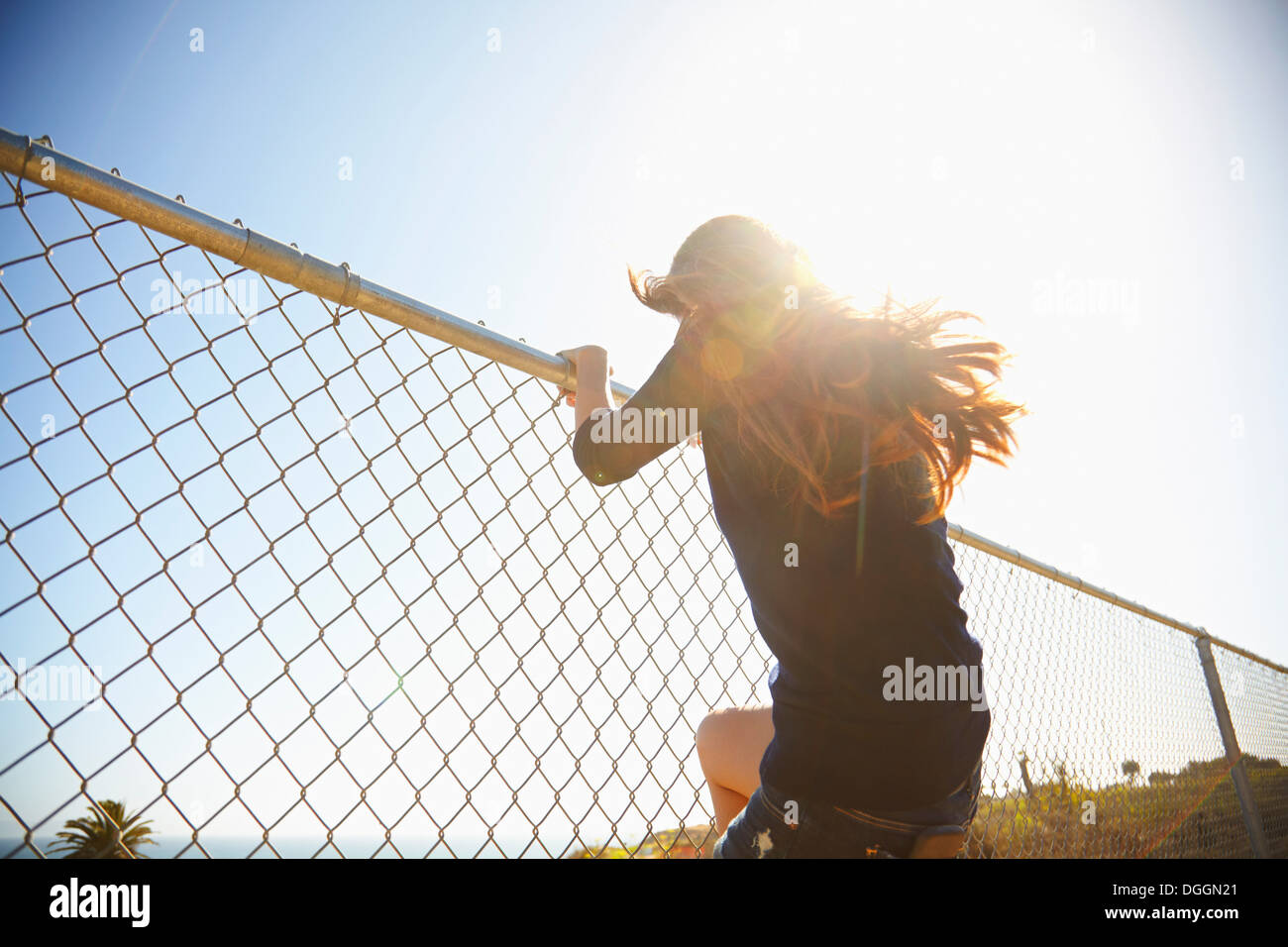 Young woman messing about on wire fence - Stock Image