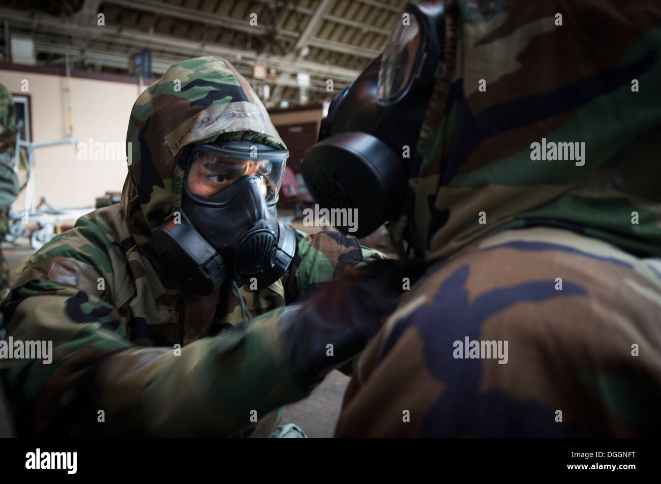 Master Sgt. Don Salvio, 374th Force Support Squadron, performs a buddy check during ability to survive and operate (ATSO) training Oct. 9, 2013 at Yokota Air Base, Japan. Donning chemical gear was one of seven stations where Airmen were reacquanted with b - Stock Image