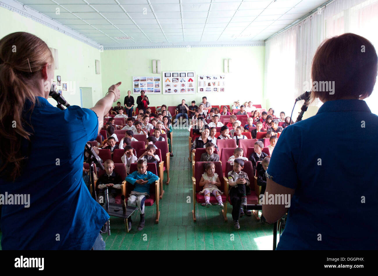 Senior Airman Megan Hokaj, left, and Master Sgt. Sherry Burt, right, sing during the Blue Yonders' performance at Chui Orphanage-Boarding School in Bishkek, Krygyzstan, Oct. 4, 2013. Burt is the noncommissioned officer in charge of the U.S. Air Forces Cen - Stock Image
