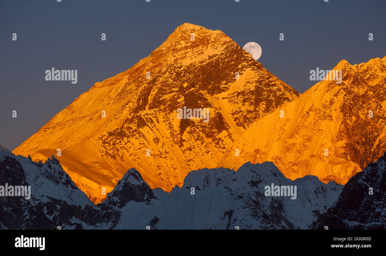 Gold pyramid of Mount Everest (8848 m) at sunset. Ascending moon. - Stock Image