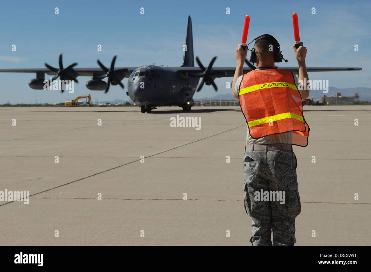 Airman 1st Class Joshua Jorgensen, 923rd Aircraft Maintenance Squadron crew chief, marshals a HC-130J Combat King II at Davis-Monthan Air Force Base, Ariz., Oct. 7, 2013. Marshaling is important because many pilots have limited vision both of the aircraft - Stock Image
