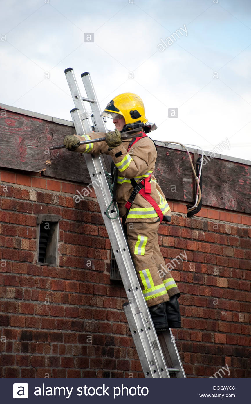 Firefighter On Ladder With Safety Harness And Crowbar