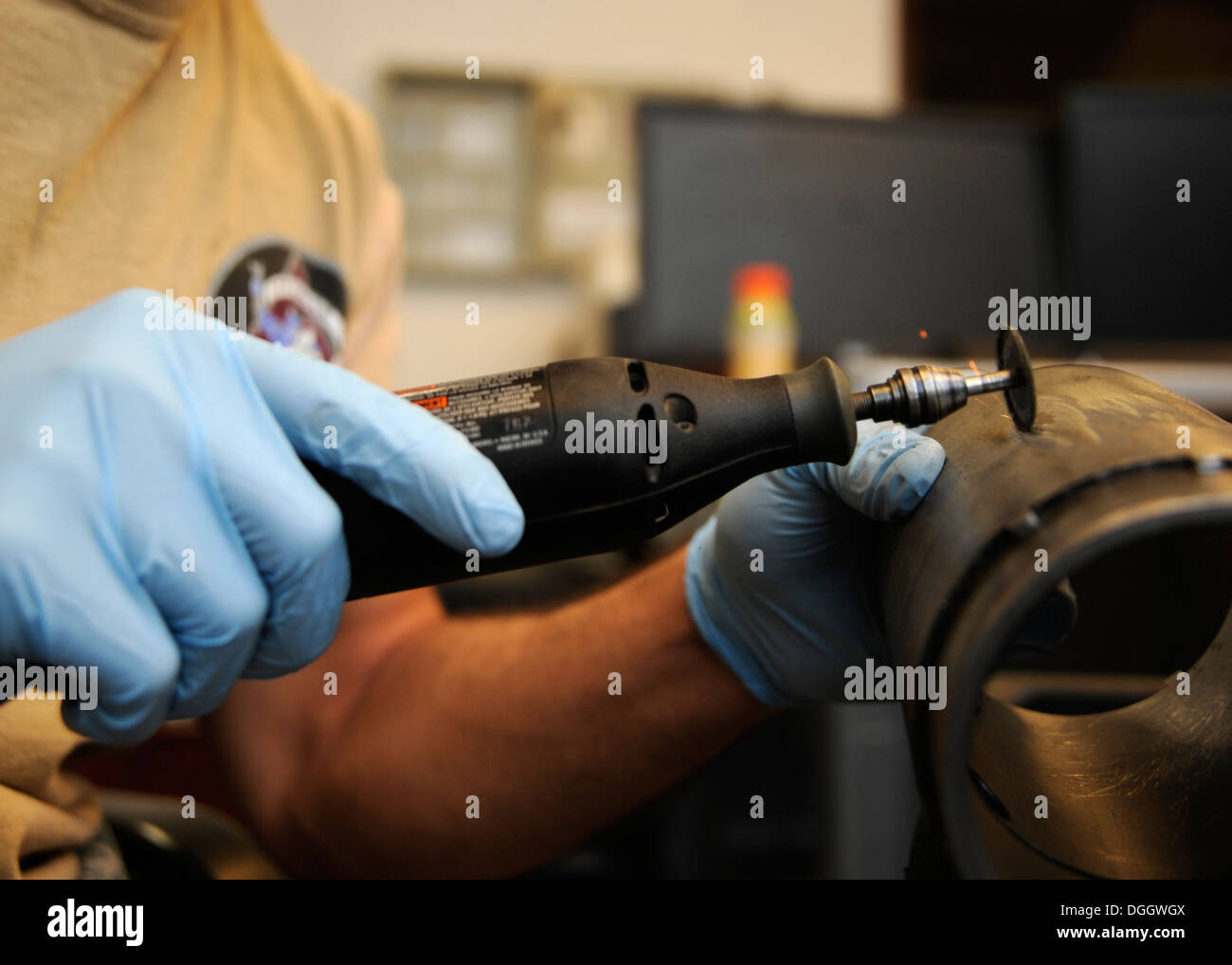 Senior Airman Nathaniel Inman uses a rotary tool to de-etch identification numbers off parts during the final stages of breaking - Stock Image