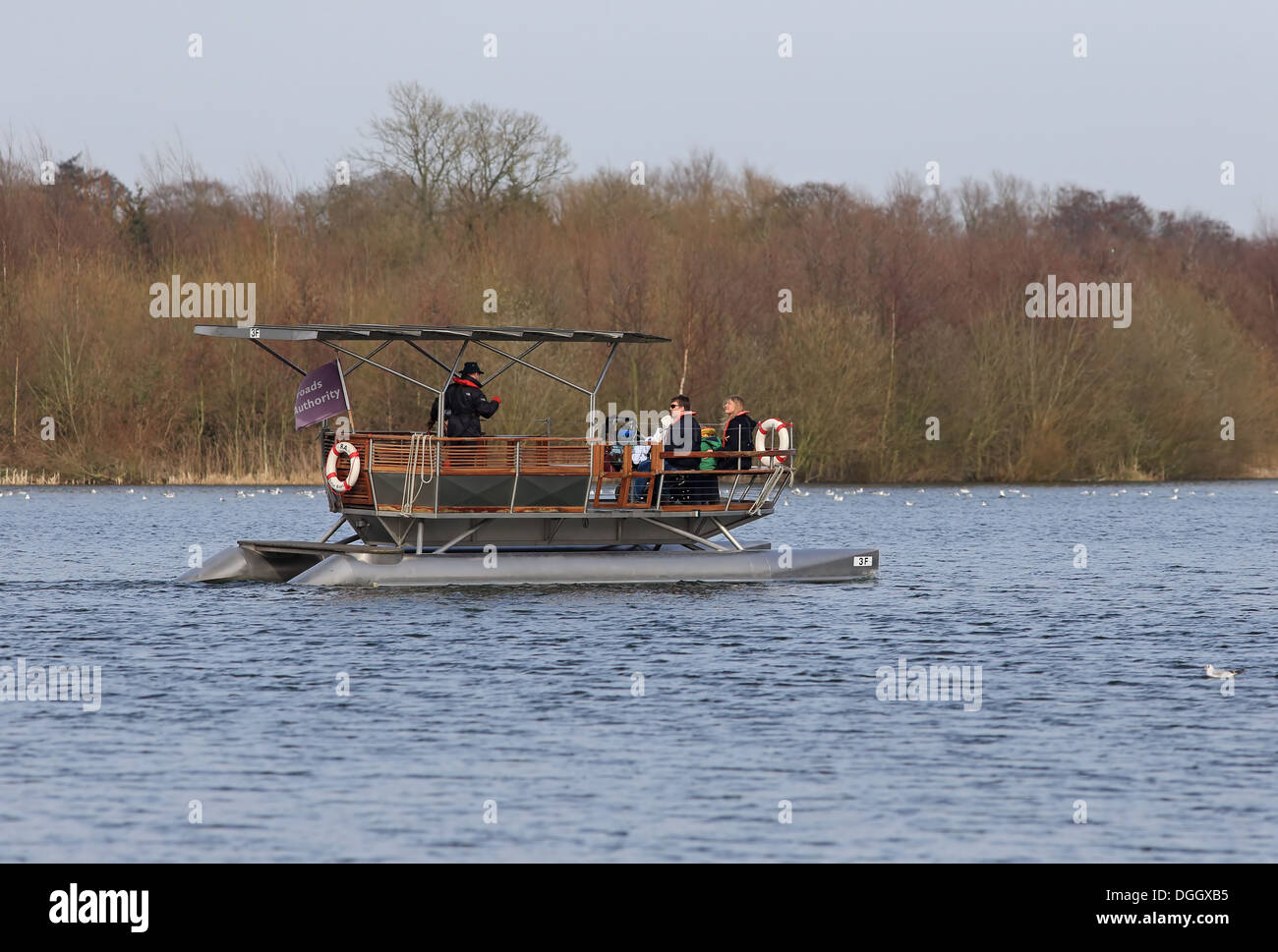 Solar-powered electric boat with tourists on river, Norwich, River Yare, The Broads, Norfolk, England, April - Stock Image