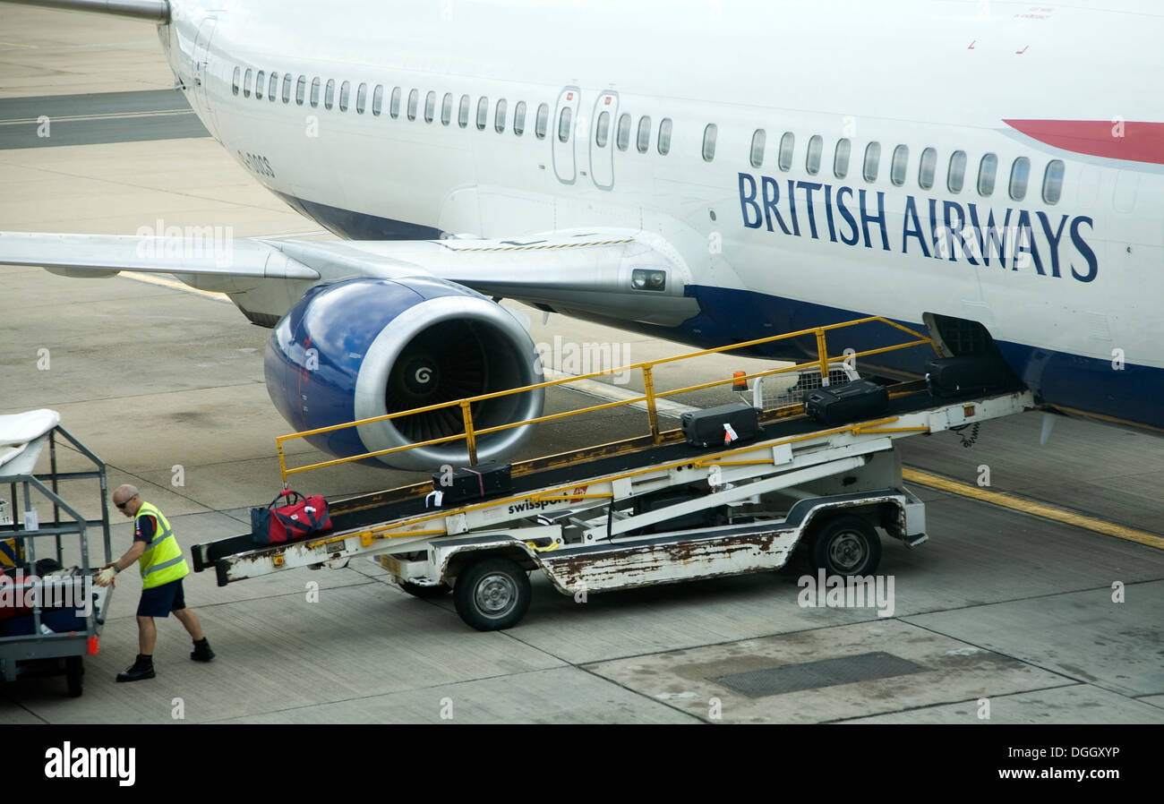 Baggage handler loading bags onto British Airways plane Gatwick airport London England - Stock Image