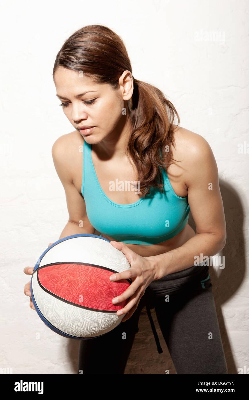 Young woman holding basketball - Stock Image