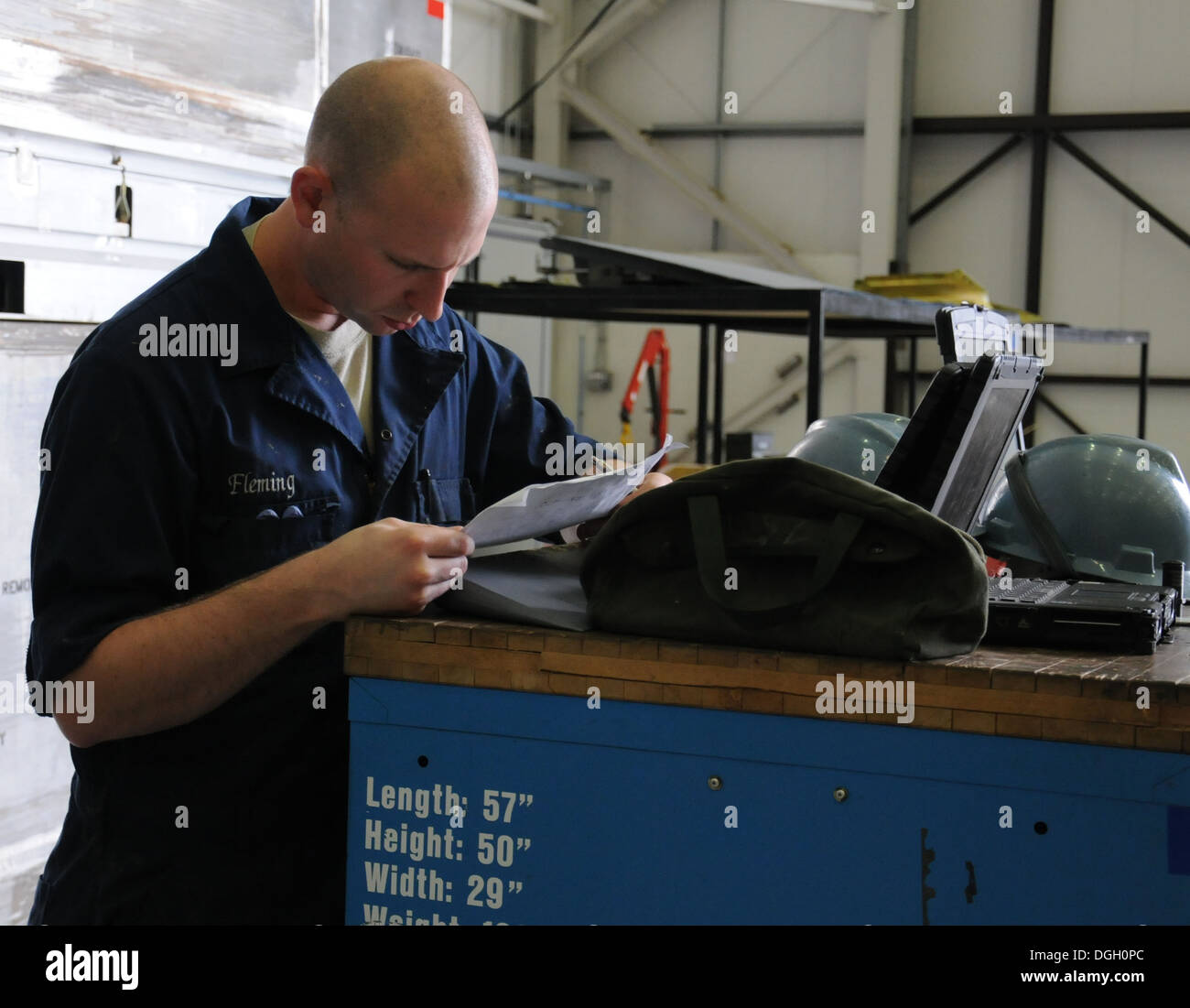 U.S. Air Force Staff Sgt. Jason Fleming, 100th Maintenance Squadron aircraft structural maintenance craftsman from Fort Oglethorpe, Ga., reviews a list of tasks for items requiring sheet metal repair Oct. 8, 2013, on RAF Mildenhall, England. The 100th MXS - Stock Image