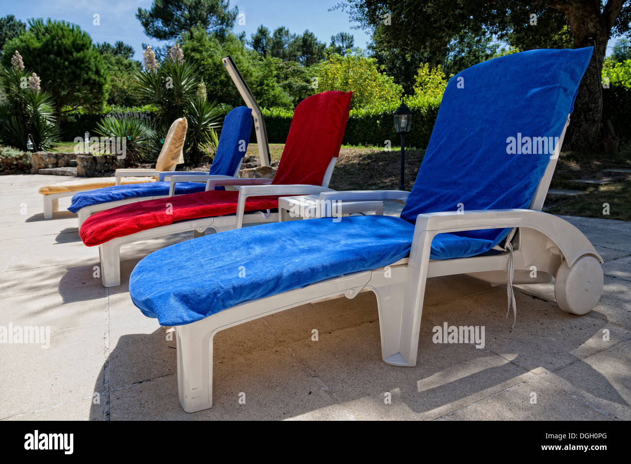 Plastic recliner chairs covered with bright blue or red fabric on a patio in the sun. & Plastic recliner chairs covered with bright blue or red fabric on a ...