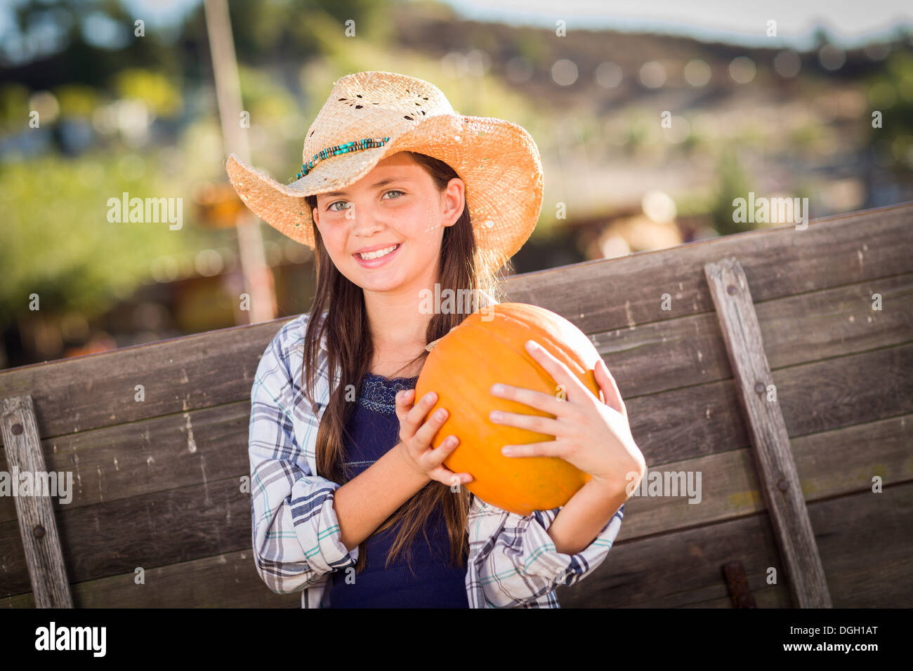 Preteen Girl Wearing Cowboy Hat Portrait at the Pumpkin Patch in a Rustic Setting. - Stock Image