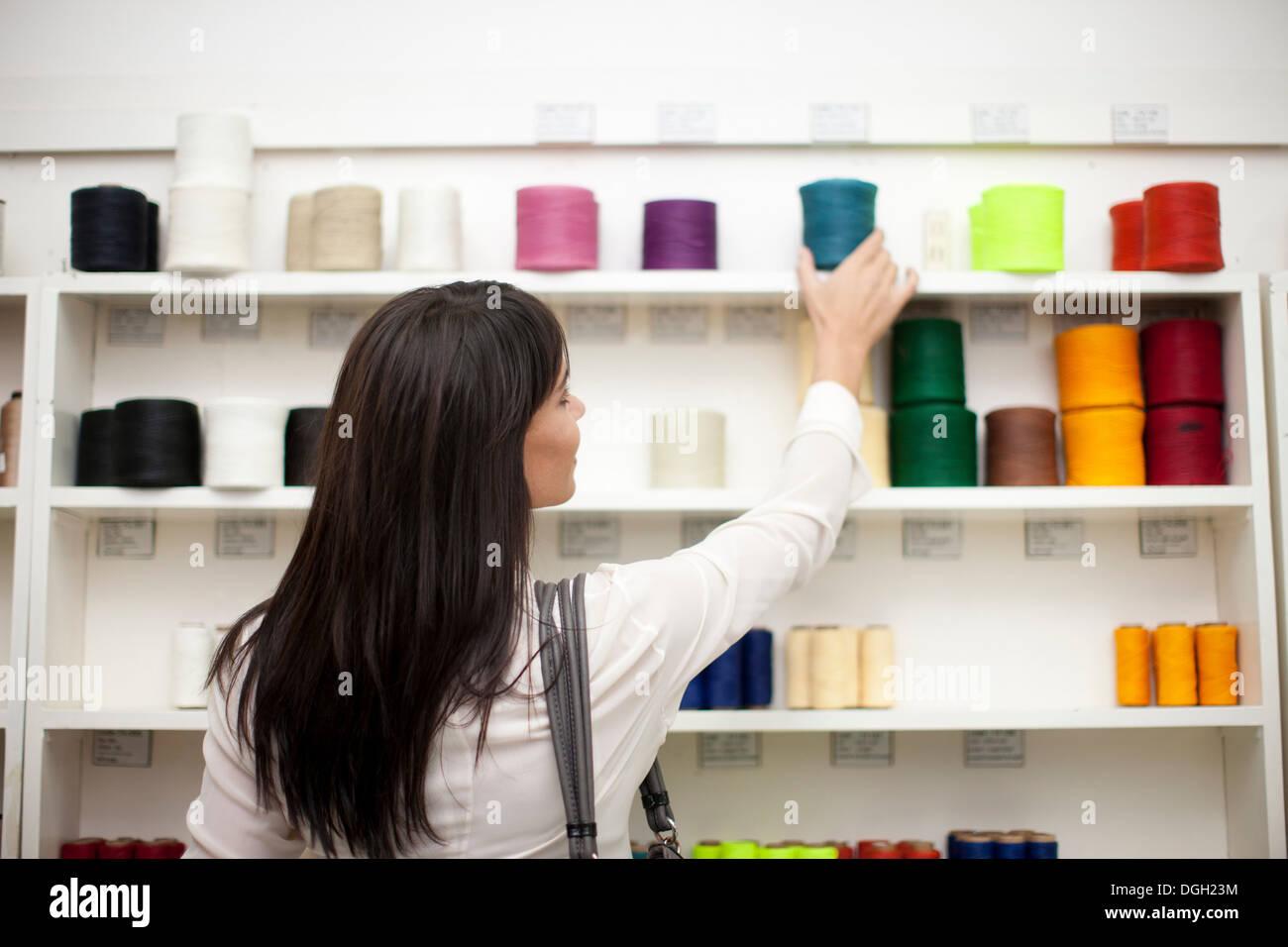 Woman choosing spool of thread in store - Stock Image