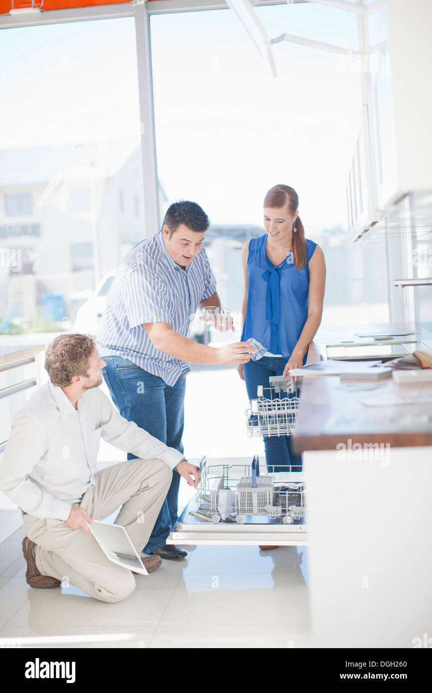 Couple and salesman looking at dishwasher in kitchen showroom - Stock Image