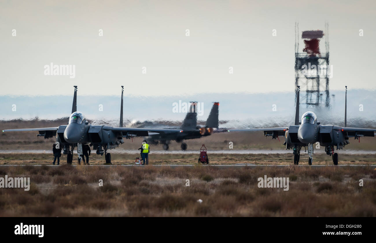 Maintenance crews perform final preflight checklists on Republic of Singapore Air Force F-15SGs while a U.S. Air Force F-15E Strike Eagle takes off behind them at Mountain Home Air Force Base, Idaho, Oct. 16, 2013. The flight was part of Mountain Roundup, - Stock Image