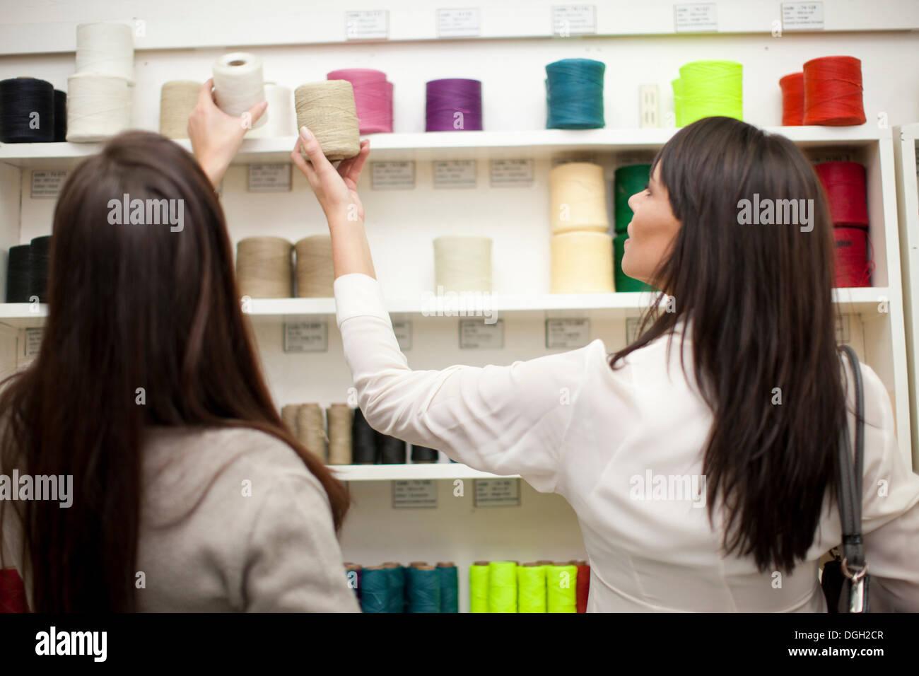 Women choosing spool of thread in store - Stock Image