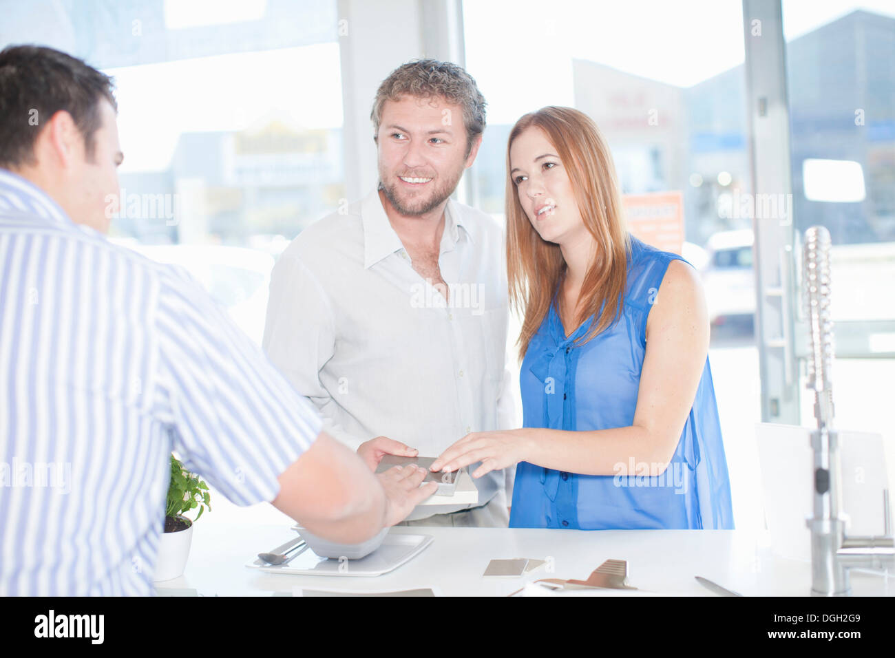 Young couple talking with salesman in kitchen showroom Stock Photo