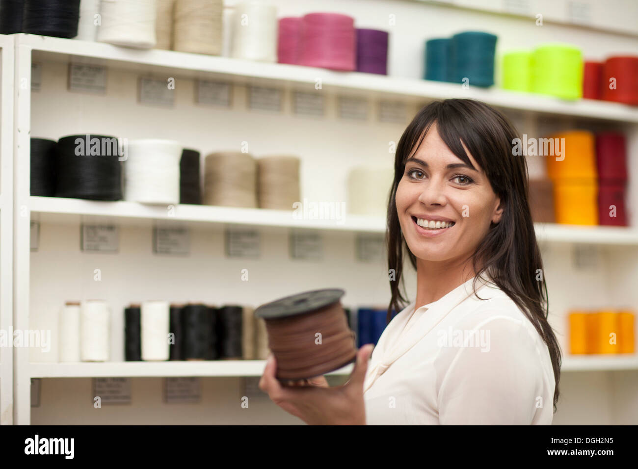 Woman holding spool of thread - Stock Image