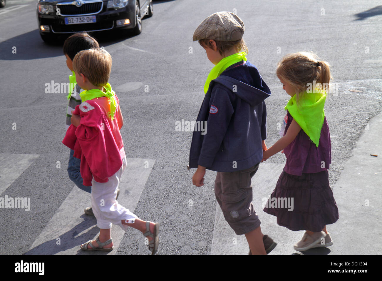 Paris France Europe French 8th 9th 17th 18th arrondissement Place de Clichy boy girl daycare crossing street holding hands scarf - Stock Image